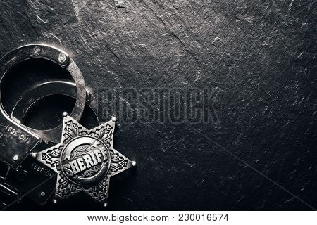 Sheriff star and handcuffs on black slate table closeup. Law concept background