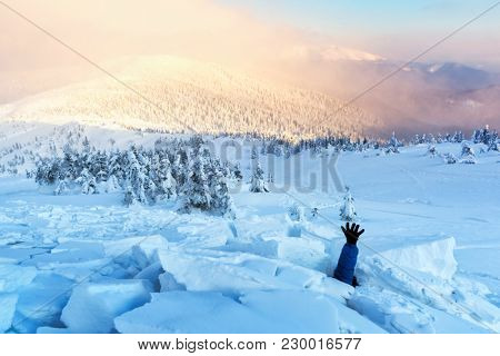 A man covered with a snow avalanche stretches out his hand to help. Danger extreme concept