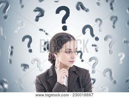 Thoughtful Young Woman With Long Dark Hair Wearing A Suit Is Thinking. She Is Looking Sideways And T