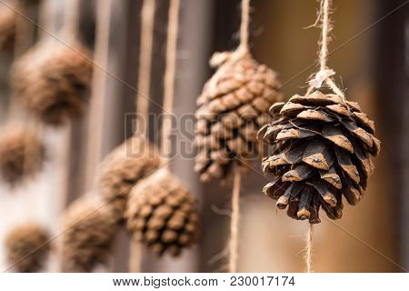 Close Up Image Of Small Pine Cone Hanging On Rope Christmas Background