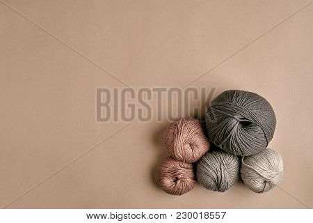 Grey And Brown Knitting Wool And Knitting Needles On Beige Background. Knitting As A Kind Of Needlew