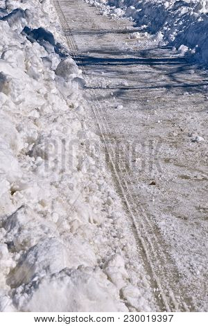 The Tire Tracks Of A Snowplow Remain After The Wet Heavy Snow Has Been Removed By A Blade After A Sn