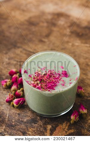 Green Cocktails With Dry Roses In A Glass Cup On An Old Wooden Table,