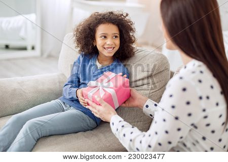 For My Honey. Pretty Alert Curly-haired Girl Sitting On The Sofa And Smiling And Her Mother Giving H