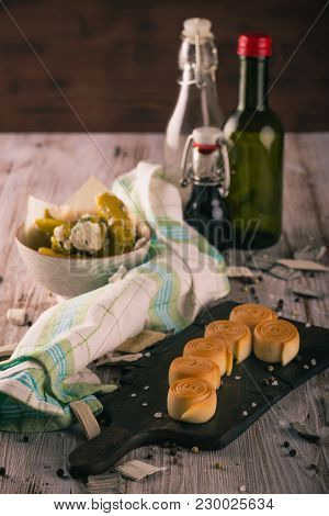 Few Pieces Of Smoked Rolled Cheese On Chopping Board