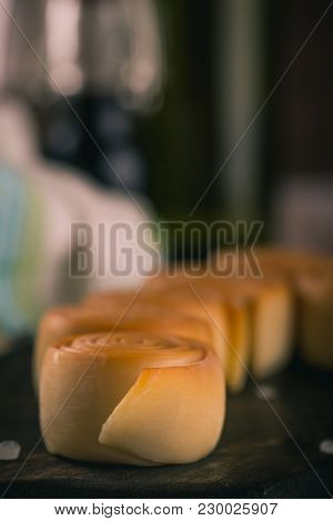 Row From Several Smoked Cheese Rolls On Dark Wooden Board