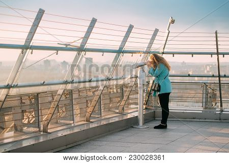Minsk, Belarus. Young Woman Looking At Coin Operated Telescope From Viewpoint Platform On National L