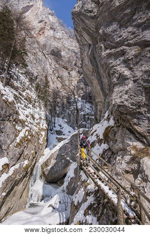 Young Women Hiking Over Wooden Ladders And Bridges Through Snow Covered Gorge Baerenschuetzklamm Wit