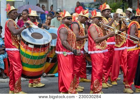 Pointe-a-pitre, Guadeloupe, February 11, 2018: Male Musicians In Fancy Dresses Playing Drums And Tru