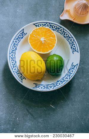 Lemons, Lime, Orange In A Plate, A Citrus Juicer On A Gray Concrete Background. Make Fresh Lemonade.