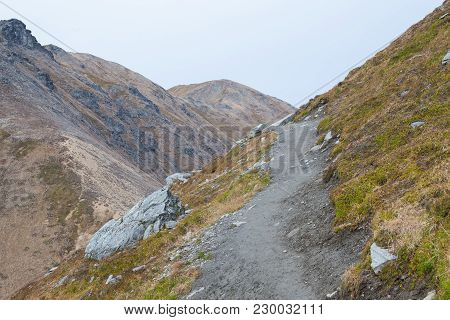 A Trail Leading To The Top Of A Mountain Peak. No Hikers Are Present. It Is An Overcast Day, And The