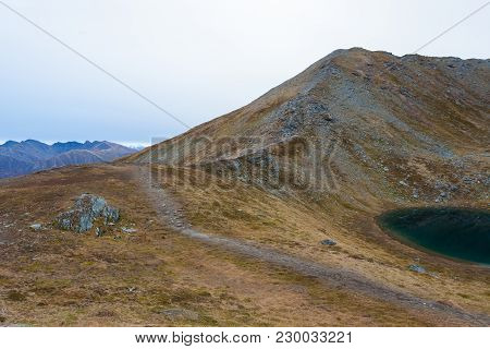 A Trail Leading Along The Ridge Of A Mountain Leading To The Peak. A Bluish Glacier Pond Is On The R