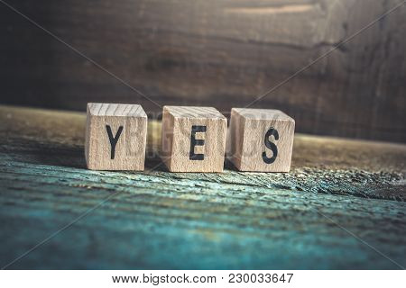 Macro Of The Word Yes Formed By Wooden Blocks On A Wooden Floor