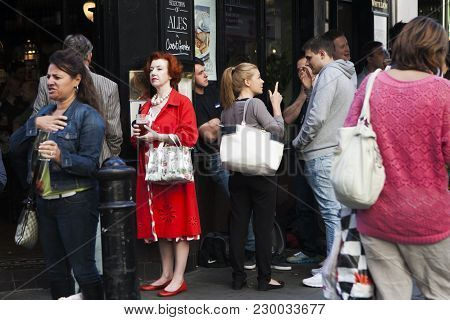 London, Uk - April 22, 2016: Middle-aged Woman In A Red Dress Drinking Beer In The Crowd Outside The