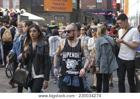 London, England - July 12, 2016 A Shaven-headed Man In Tattoos Wearing A Black T-shirt With A Girl I