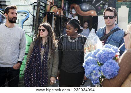 London, England - July 12, 2016 Fashionable Girls Walking Through Brick Lane
