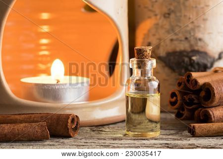 A Bottle Of Cinnamon Essential Oil With Cinnamon Sticks And An Aroma Lamp In The Background