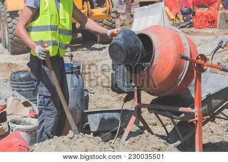 Construction Worker On A Cement / Concrete Mixer Doing Hard Job.