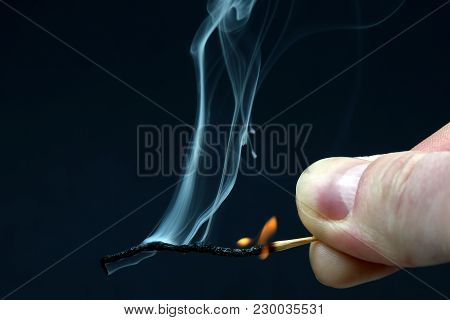 Burning And Smoking Wooden Match In Hand On Dark Background