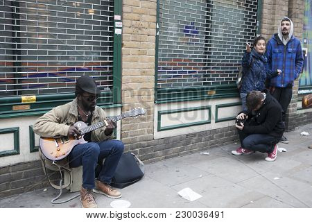 London, England - July 12, 2016 The Street Musician Plays The Guitar. Tourists In Blue Checkered Shi