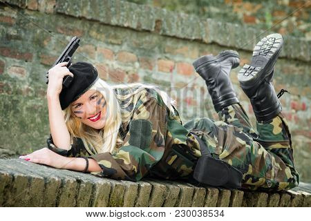 The Smiling Blonde Woman In Military Uniform With Gun Is Posing On Brick Wall Outdoors.