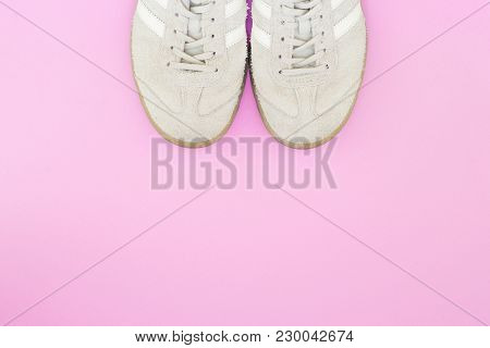 Light Sneakers On A Bright Pink Background. Minimalistic Composition With Sneakers And Spotted Text.