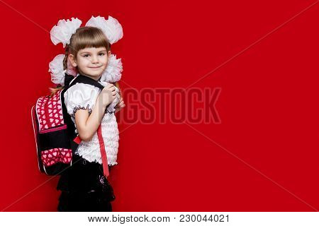 A Cute Smilng Little Girl In School Uniform And White Bows With A Backpack On Red Background. Back T