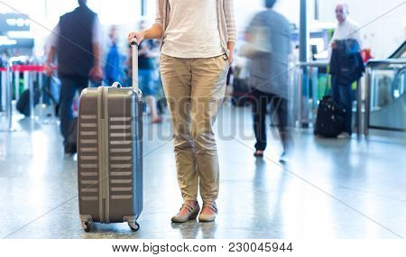 Young female passenger at the airport, waiting for her delayed flight
