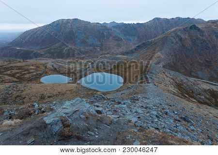 A Trail Leading Along The Ridge Of A Mountain Leading To The Peak. Two Bluish Glacier Ponds Are On T