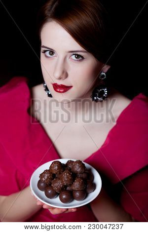 Young Surprised Woman In Red Victorian Epoch Clothes With Chocolate Candy On Dark Background