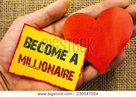 Handwriting text showing Become A Millionaire. Business concept for Ambition To Become Wealthy Earn Fortune Fortunate written Sticky Note Paper With Heart Holding Hand with Finger. poster