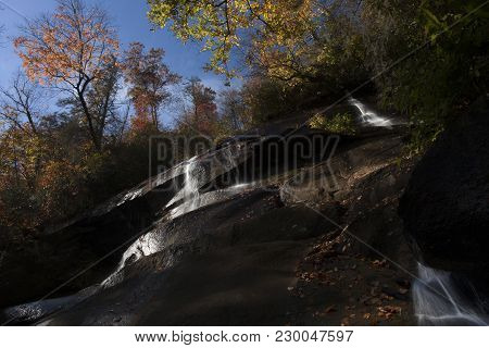 Streams Of Water Flow Over The Rocky Cliff In The Pisgah Forest During Autumn