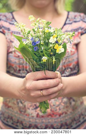 A Bouquet Of Lilies Of The Valley And Forest Violets In A Woman's Hand.