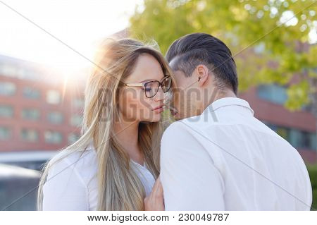 Young Blonde Woman Whispers To Man Love Outdoors In City, Declaration Of Love
