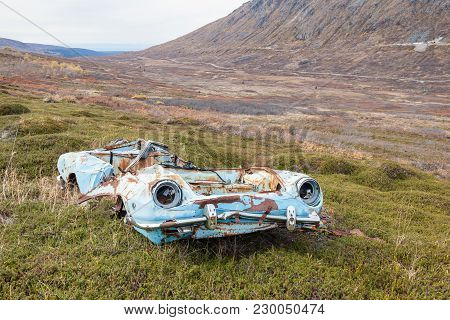 A Old Blue Car That Appears To Have Rolled Off The Road And Been Smashed In The Process. In The Back