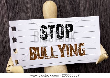 Word, writing, text  Stop Bullying. Conceptual photo Awareness Problem About Violence Abuse Bully Problem written torn paper holding by sculpturethe wooden background poster