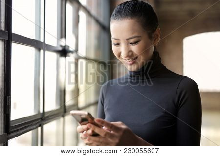 Smiling woman checking her phone