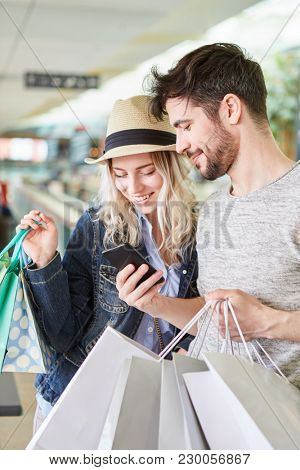 Young couple uses shopping app for price comparison on the smartphone