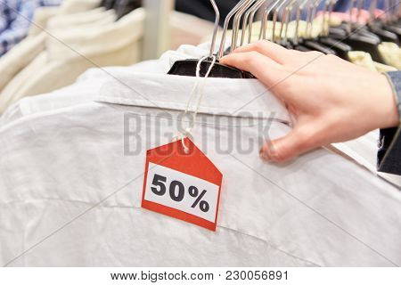 Hand on clothes with 50% discount Discount on retail in a shop