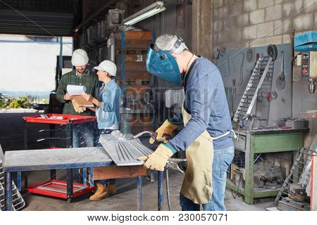 Welder or metalworker with protective clothing in workshop
