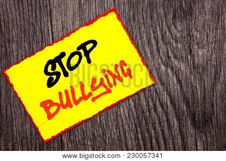 Conceptual hand writing text showing Stop Bullying. Concept meaning Awareness Problem About Violence Abuse Bully Problem written Yellow Sticky Note Paper the wooden background. poster