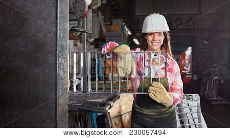 Young woman as metalworker in metallurgy factory
