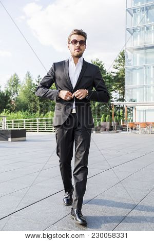 Male Businessman Or Worker In Black Suit, Shirt And Sunglasses Fastens A Button On His Jacket With H