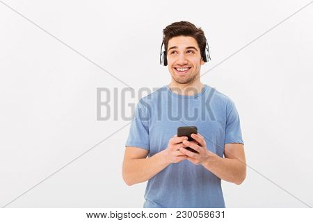Caucasian smiling man in casual t-shirt listening to music via wireless earphones using smartphone isolated over white background