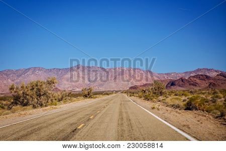 A Highway Cutting Through The Mojave Desert With A Large Mountain In The Foreground In A March Lands