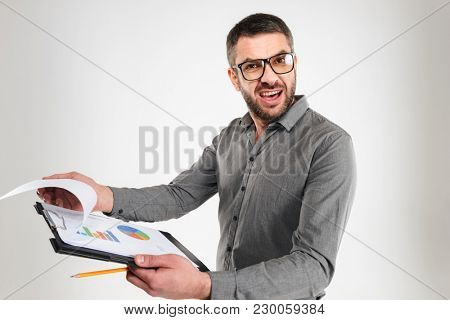 Image of displeased confused businessman standing isolated over white background reading documents.