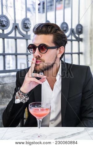 Handsome Young Man In Black Suit With White Shirt, Bracelets And Accessories On Hands In Sunglasses
