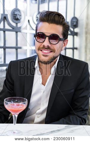 Handsome Young Smiling Man In Black Suit With White Shirt, Bracelets And Accessories In Sunglasses A