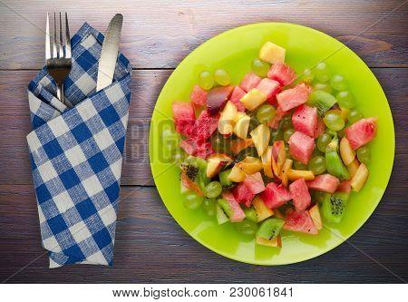 Fruit Salad On A Wooden Background. Vegetarian Salad Of Fruit On A Plate