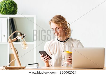 Photo of smiling young business woman sitting in office using laptop computer looking aside chatting by mobile phone drinking coffee.